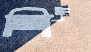 A painted road sign indicates an electric-vehicle recharging parking point.