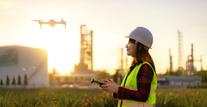 Drone flying over oil refinery plant during site survey.