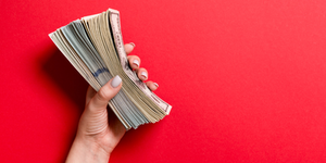 Hand Holding Money Bills Cash On Red Background © Mykola Sosiukin Dreamstime