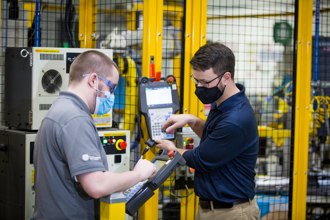 """Two employees on the Industry 4.0 Development program – Jordan Klotz ( left) and Collie Crawford ( right) discuss shortcuts for """"pick and place"""" routines on the robots teach pendant for the new automated dishwasher spray arm assembly cell."""