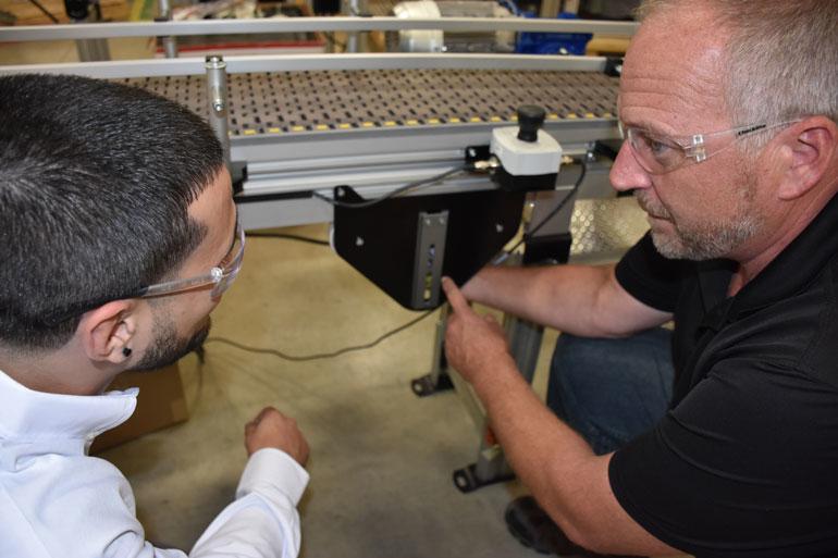 Un ingénieur chevronné souligne les accessoires qui ont été ajoutés à cet accessoire de pointage sur un convoyeur à chaîne en plastique.