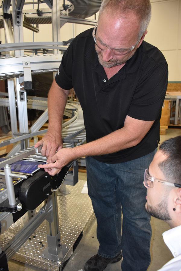 Un ingénieur montre à un stagiaire comment fonctionne le point de transfert sur un convoyeur à chaîne en plastique.