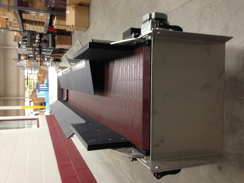 Le convoyeur hybride a ses parois latérales enduites de nylon repliées pour réduire sa largeur.  Cela facilite l'installation à l'intérieur des machines de soufflage.
