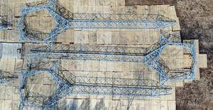 Drone's eye view of the fly yard shows tangent towers ready for the helicopter to pick them up and take them to their foundations. This kept matting to only certain areas so that the towers could be flown to areas inaccessible to heavy ground equipment.