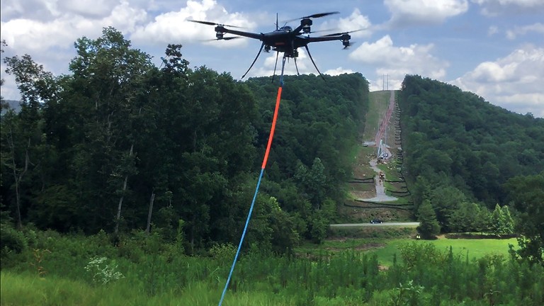 Alabama Power and Service Electric Co. partner to pull ropes across large valleys near Springville, Alabama.