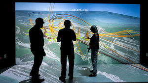 NREL scientists Evan Rosenlieb, Nicholas Brunhart-Lupo, and Amy Schwab look at a 3D visualization of a resiliency study for Tyndall Air Force Base.