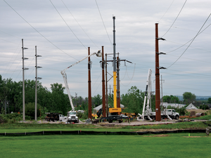 Three Phase Line crews maneuver equipment situated atop timber mats into position to pull new wire and attach it to new steel transmission structures.